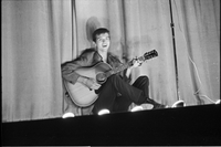 Image of a male folksinger sitting on stage and playing guitar at a hootenanny show at the New Yorker Theatre (out of focus).