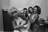 "Image of the Ladybirds rock group posing for the camera in an office at Friar's Tavern with Barbara ""Bobbi"" Branch looking up and Deborah Dayan holding a guitar."