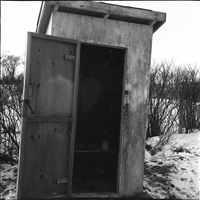 Image of an outhouse with its door wide open.