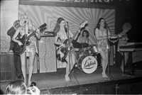 Image of the Ladybirds rock group performing topless on the stage at the Friars Tavern. A man is filming the show from the back of the stage