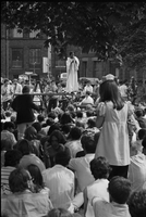 Image of the crowd watching a musician on a stage and a woman standing in the foreground at a love-in in Queen's Park.