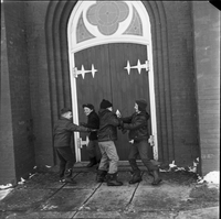 Image of four boys playing in front of the entrance to Sainte Croix Roman Catholic Church in Lafontaine, Ont.
