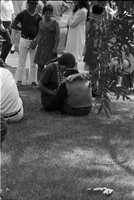 Image of a woman with a chimpanzee sitting on the grass at a love-in in Queen's Park.