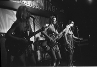 Image of three members of the Ladybirds rock group performing topless on the stage at the Friars Tavern. The photo is out of focus.