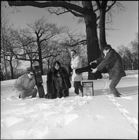 The Dirty Shames rock band playing in the snow with their instrument cases in Queen's Park.
