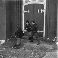 Image of three boys playing in front of the entrance to Sainte Croix Roman Catholic Church in Lafontaine, Ont.
