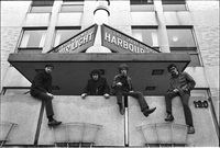 Image of City Muffin Boys sitting on a wall in front of Salvation Army Harbour Light Centre.