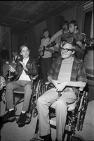 Image of two male audience members sitting in wheelchairs and clapping at an open house for paraplegics at the Cosmic Home Coffee House.