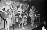Image of the Ladybirds band performing topless on the stage at the Friars Tavern.