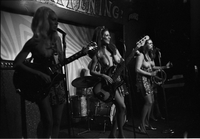 Image of three members of the Ladybirds rock group performing topless on the stage at the Friars Tavern. The photo is underexposed.