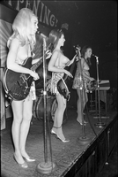 Image of three members of the Ladybirds rock group performing topless on the stage at the Friars Tavern.
