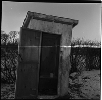 Image of an outhouse with its door wide open. There is an overexposed line in the photo.