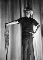 Image of a male performer wearing a wig and holding a snowshoe on stage at a hootenanny show at the New Yorker Theatre.