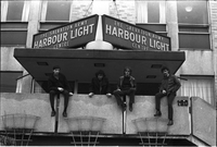 Image of City Muffin Boys sitting on a wall in front of the Salvation Army Harbour Light Centre.