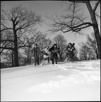 The Dirty Shames rock band holding instrument cases and running toward the camera in the snow winter time in Queen's Park.