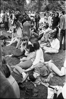 Image of people sitting and standing on the grass at a love-in in Queen's Park. Someone is holding a recorder in the foreground.