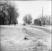 Image of a road in winter in Lafontaine, Ontario, with a man, car, houses and trees in the background.