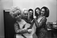 Image of the Ladybirds rock group posing for the camera in an office at Friar's Tavern with Deborah Dayan holding a guitar.