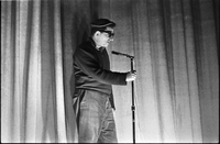 Image of a man holding a microphone in his right hand on stage at a hootenanny show at the New Yorker Theatre.