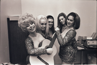 Image of the Ladybirds rock group posing for the camera in an office at Friar's Tavern with Deborah Dayan holding a guitar with her eyes closed.