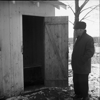 Image of an older man standing in front of the open door of a wooden outhouse in the winter.