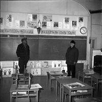 Image of a man and a priest standing in front of a blackboard in a classroom in an elementary school in Lafontaine.