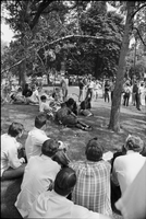 Image of people sitting on the grass at a love-in in Queen's Park.