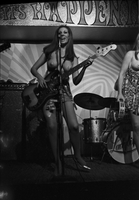 Image of Lisa Lynn topless and playing bass with the Ladybirds rock group on the stage at the Friars Tavern.