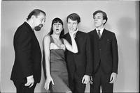 Image of the Dirty Shames rock band posing for a formal portrait with Carol Robinson making a comical face and holding Jim McCarthy's chin as Amos Garrett and Chick Roberts look on.