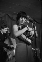 Image of Carol Robinson holding an autoharp and performing on the stage of the Dell Tavern with the Dirty Shames.