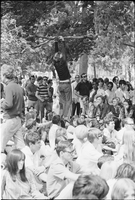 Image of the crowd at a love-in at Queen's Park and one man is climbing a tree.