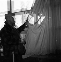 Image of a man holding up a window curtain for the camera. There is a large rip in the curtain. Photo is out of focus.