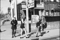 A group of women hold signs and picket on the sidewalk in front of the Mynah Bird coffeehouse in Yorkville.
