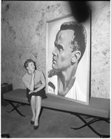 A woman sitting on a bench smiling and looking at the Harry Belafonte poster.