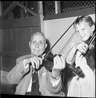 An older man and young girl holding fiddles and posing for the camera.