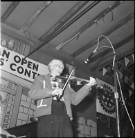 A fiddler performing on stage at the Shelburne arena during the Canadian Open Old Time Fiddlers' Contest.