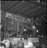 A fiddler and accompanist on piano on stage at the Shelburne arena during the Canadian Open Old Time Fiddlers' Contest.