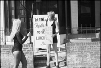 Two women with picket signs outside the Mynah Bird coffeehouse in Yorkville protesting higher wages for male nude staff.