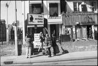 A group of women picket on the sidewalk in front of the Mynah Bird coffeehouse in Yorkville while a man films the scene.