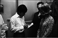 Billy Hinsche (white shirt) writing on a piece of paper while a young woman looks on - backstage at Maple Leaf Gardens.