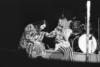 Cass Elliot (left) holding the hand of Michelle Phillips (right) in performance with The Mamas and the Papas at Maple Leaf Gardens