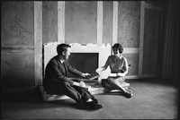 Glendon Construction - male student hands a book to Lois Henry in front of an unfinished fireplace.
