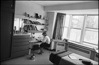Female student studying at the desk in her dorm room, electric kettle on the floor.