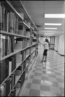 Female student taking a book off a bookshelf in the library.