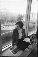 Female student, Gail Cuddy, sitting on a library windowsill overlooking Glendon Hall's courtyard.