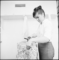 Close-up image of a female student ironing clothes in residence.