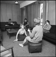 Five female students in a residence common room, one is playing guitar.