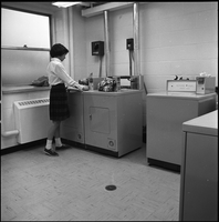 Female student, at one of the machines in laundry room.