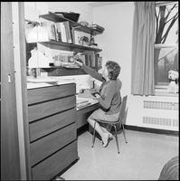 Female student, at desk, reaches up to adjust radio.