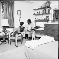 Two female students in a residence room, consulting a book.